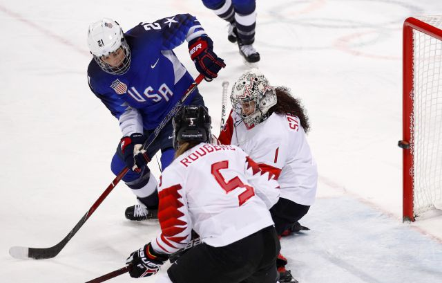 Hilary Knight (21), of the United States, shoots the puck past goalie Shannon Szabados (1), of Canada, for a goal during the first period of the women