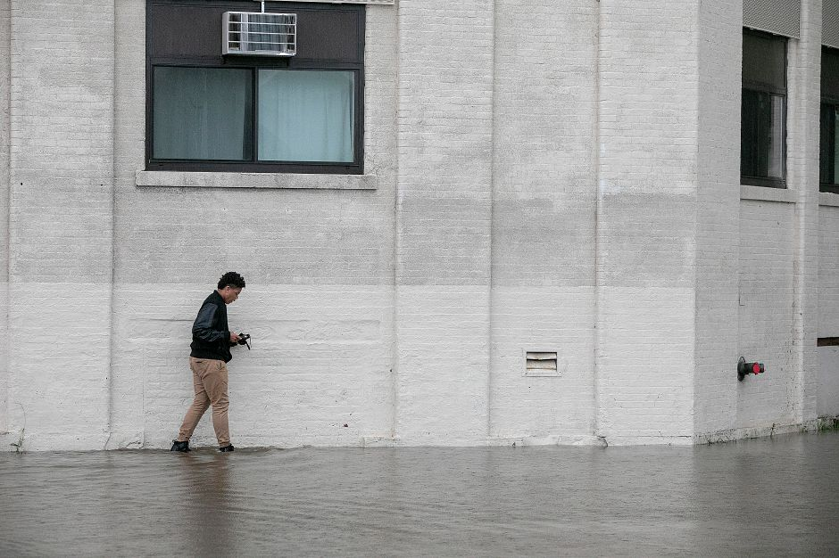 A pedestrian walks through flood waters next to the Kennedy Building in downtown Meriden, Tuesday, Sept. 25, 2018. Heavy rain Tuesday evening closed roads and flooded basements of local homes. Dave Zajac, Record-Journal
