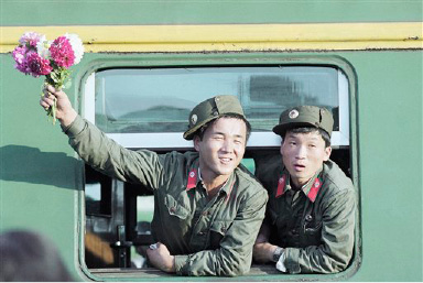 Two young North Korean soldiers, one waving flowers given to him by friends, at the window of a train before leaving Kaesong on August 22, 1990 for Pyongyang, the North Korean capital. The soldiers had ended a tour of duty at Kaesong, which is near the border dividing North and South Korea. (AP Photo/Vincent Yu)