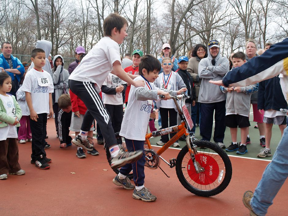 FILE – Blake Carrigan, 10, of Shelton jumps on his brother's Shane Carrigan's back to celebrate Shane, 7, winning a bicycle during the Meriden Rotary Club Annual 5K Road Race and Fun Run Sunday morning in Hubbard Park. Target stores donated six bicycles to the rotary club, which raffled them off to participants of the Kids' Fun Run earlier in the day. (Richie Rathsack/Record-Journal)