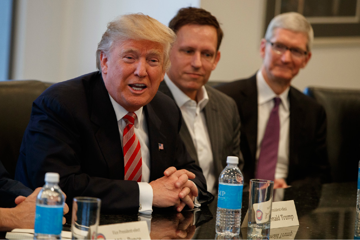Apple CEO Tim Cook, right, and PayPal founder Peter Thiel, center, listen as President-elect Donald Trump speaks during a meeting with technology industry leaders at Trump Tower in New York, Wednesday, Dec. 14, 2016. (AP Photo/Evan Vucci)