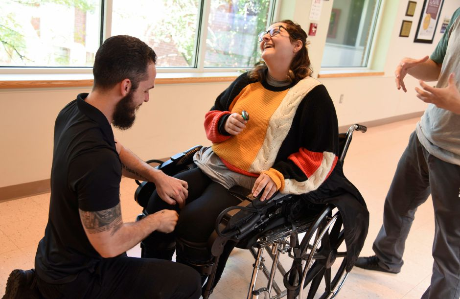 Physical therapist Tim Kilbride, left, helps Kayla Carbaugh, 21, originally of Wallingford, strap into a Ekso Bionics exoskeleton during an outpatient therapy session at Gaylord Speciality Healthcare in Wallingford on Sept. 13, 2019. Kilbride is spinal cord injury specialist for the inpatient therapy department at Gaylord. | Bailey Wright, Record-Journal