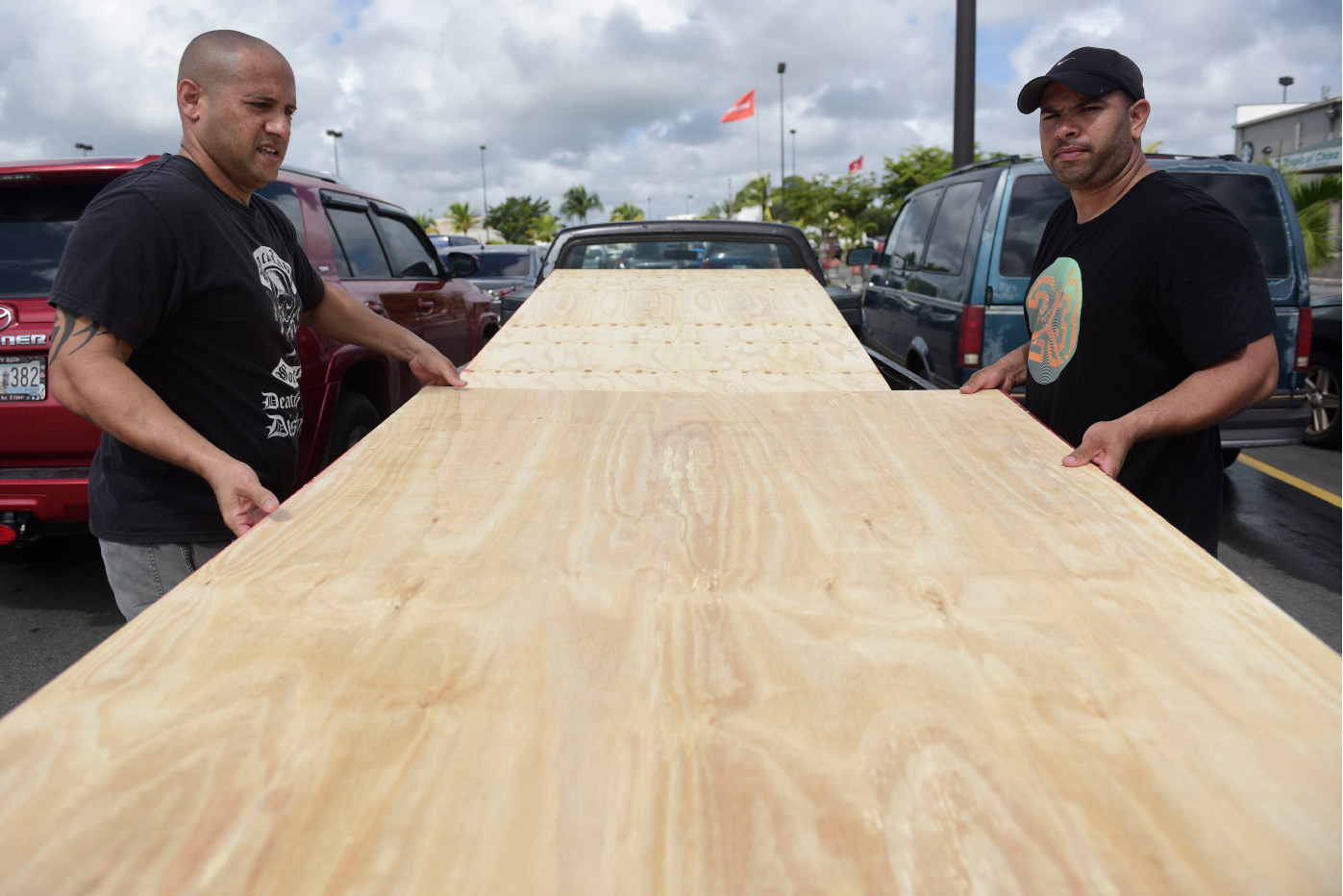 Luis Enrique Garcia, left, and Jose Rivera, load wood panels to be used for boarding up windows in preparation for Hurricane Irma, in Carolina, Puerto Rico, Tuesday, Sept. 5, 2017. Irma grew into a dangerous Category 5 storm, the most powerful seen in the Atlantic in over a decade, and roared toward islands in the northeast Caribbean Tuesday. (AP Photo/Carlos Giusti)