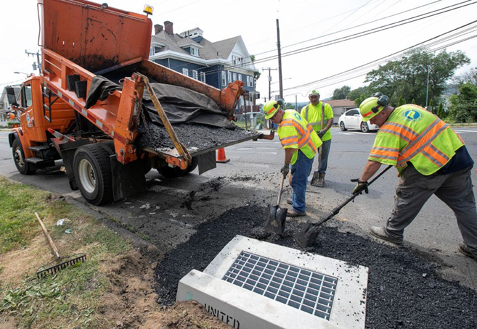 Connecticut Department of Transportation workers spread asphalt around a storm drain while working in hot and humid conditions on Broad Street in Meriden on Wednesday. Photos by Dave Zajac, Record-Journal