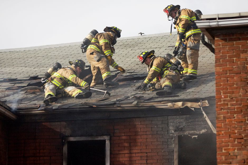 Meriden Fire Fighters vent the roof and extinguish the remaining flames of a multi-family home on Broad Street in Meriden near the corner of East Main Street. One badly burned man taken from the building by fire fighters was rushed from the scene in an ambulance. (Johnathon Henninger/ Record-Journal)