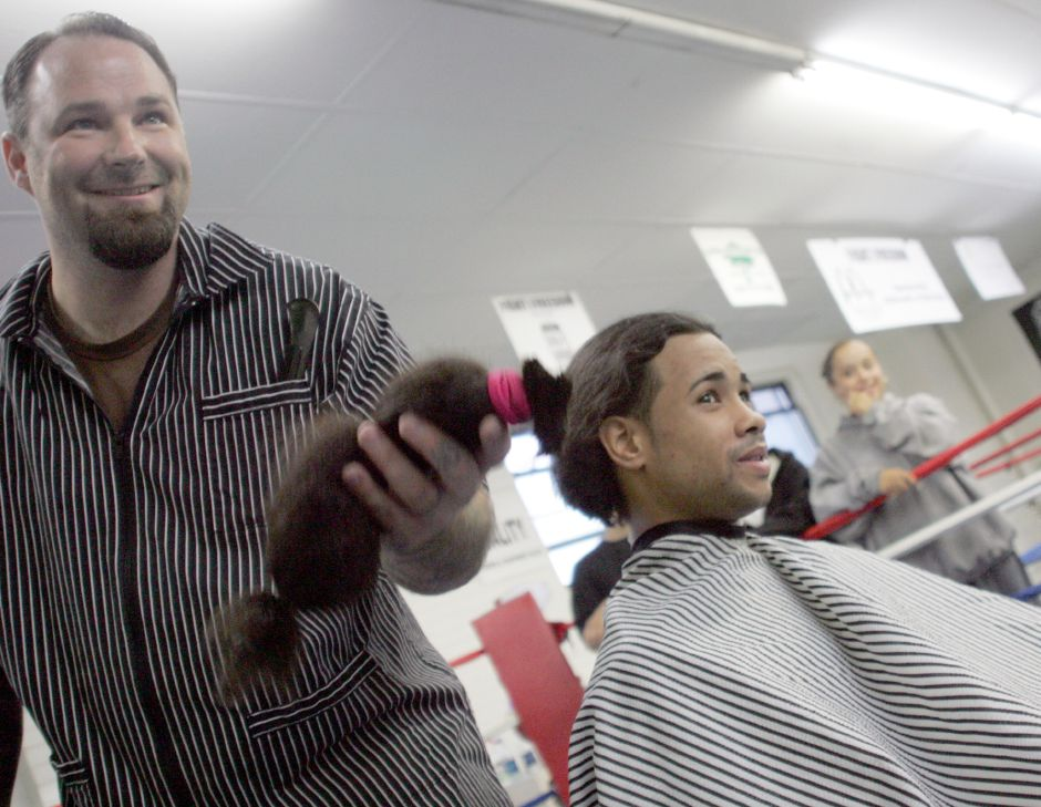 FILE PHOTO: Glenn Agnew, barber/owner of Village Barber Shop, tosses a long section of Meriden resident Jose Lara's hair to Lara's mother at Beat the Street Community Center. Rob Beecher / Record-Journal