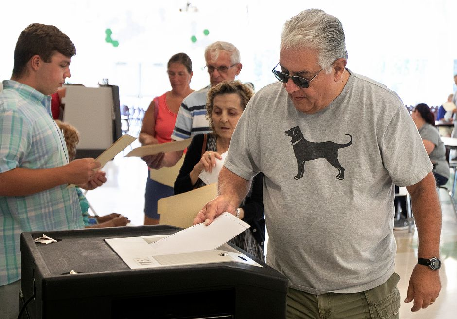 Bill Coviello inserts his ballot into a scanner at Maloney High School on Wednesday as Meriden voters went to the polls to decide whether to send the adopted 2018-19 budget back to the City Council for changes. Dave Zajac, Record-Journal