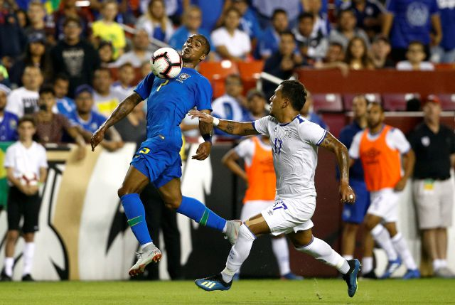 Brazil forward Douglas Costa, left, tries to maintain possession as he is pressured by El Salvador defender Juan Barahona in the first half of a soccer match, Tuesday, Sept. 11, 2018, in Landover, Md. (AP Photo/Patrick Semansky)