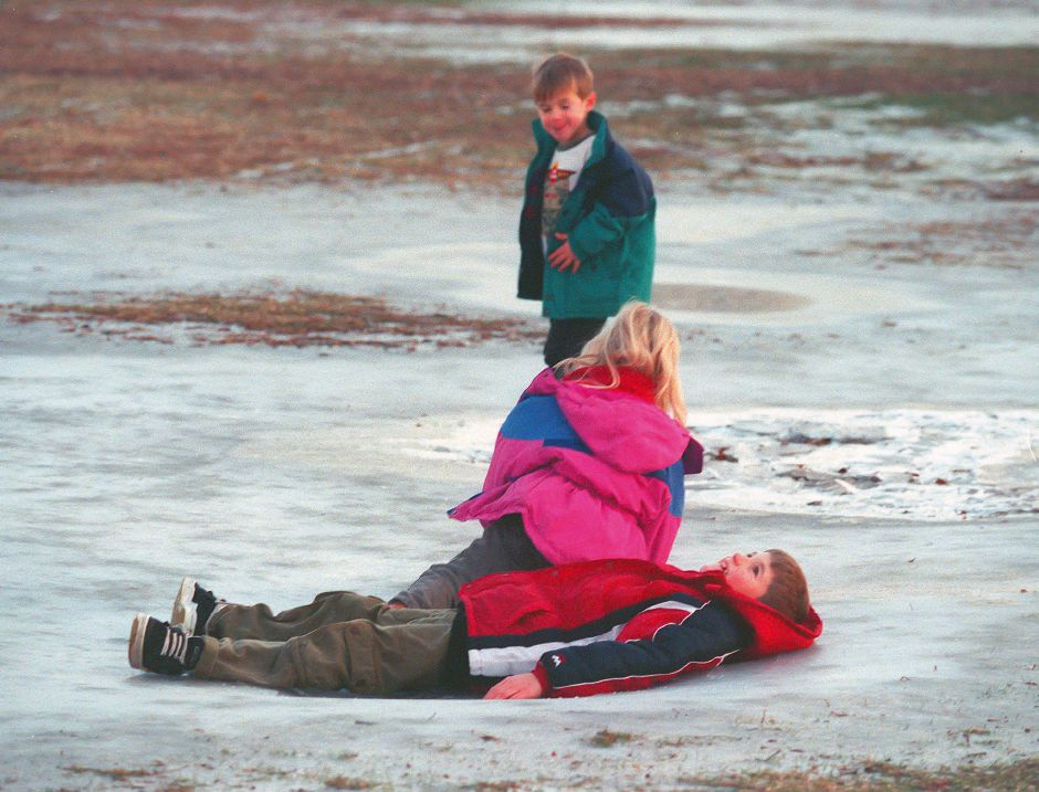 RJ file photo - William Grenier, 8, relaxes on the ice while his sister, Cassie, 5, and brother Benjamin, 4, try to stay upright on a shallow frozen puddle at Habershon Field in South Meriden Jan. 12, 1999.