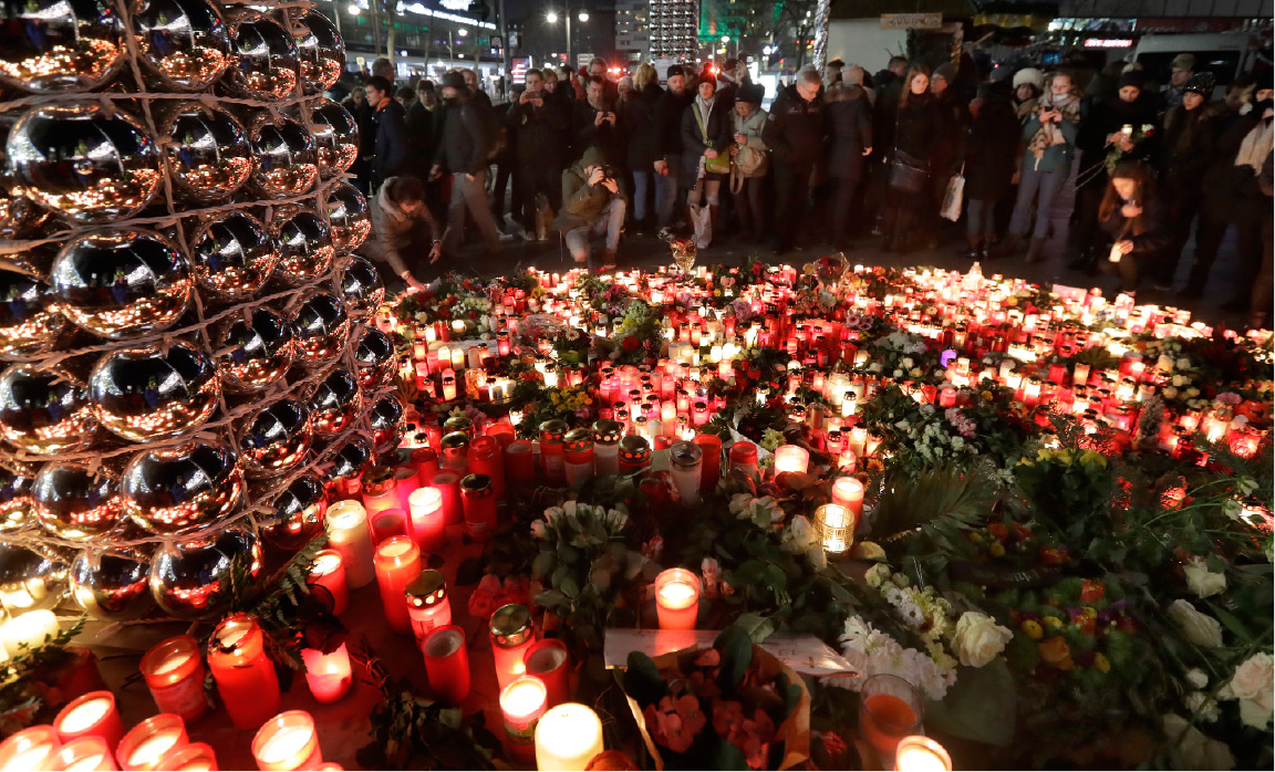 People stay in front of candles close to a Christmas market beside the memorial church in Berlin, Germany, Wednesday, Dec. 21, 2016, two days after a truck ran into a crowded Christmas market and killed several people. (AP Photo/Michael Sohn)