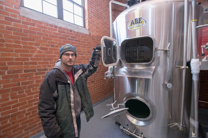 Josh Norris, co-owner, stands next to the American Beer Equipment brew house system Wednesday, Dec. 28, 2016, at Witchdoctor Brewing Company in Southington. The company expects to be brewing beer by the end of January. Dec. 28, 2016 | Justin Weekes / For the Record-Journal