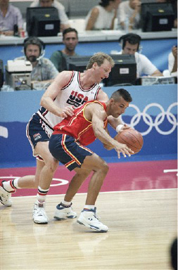 8f763d6e9e2b U.S. Olympic basketball player Larry Bird reaches around player Tomas Prats  from Spain