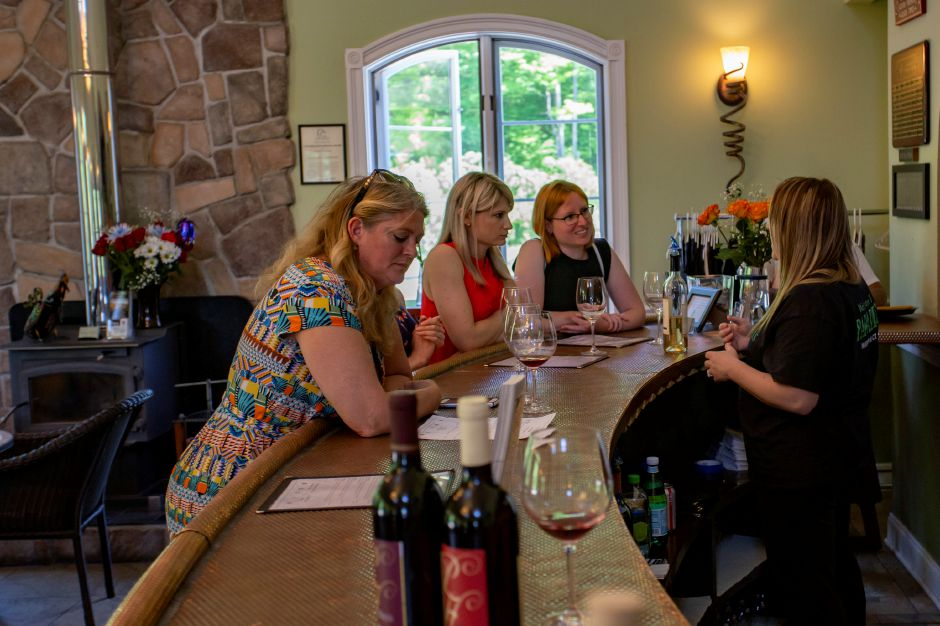 Natalie Ruggiero explains the Paradise Hills Vineyards wine to visitors  on Thursday at the Wallingford winery. Photos by Richie Rathsack, Record-Journal