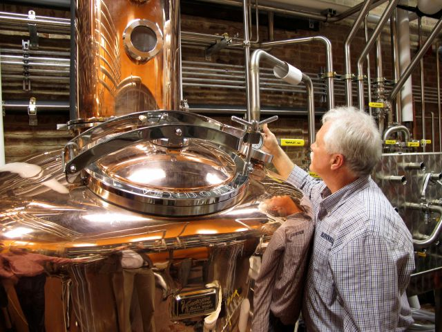 FILE - In this Wednesday Nov. 13, 2013, file photo, Charlie Downs, the artisanal craft distiller at a new Heaven Hill Distilleries tourism attraction in downtown Louisville, Ky., checks gauges on a still that will produce small batches of whiskey. In an effort to woo Amazon
