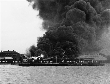 "The Shanghai warfront, shows the explosion which resulted when a bomb hit the Asiatic Petroleum Company property along the Whangpoo River, on Sept. 1, 1937. This picture was taken from the deck of the German steamer ""Kulmerland"" by Ray Slater Murphy, New York socialite, as she fled the city, the first refugee to return to the U.S. (AP Photo)"