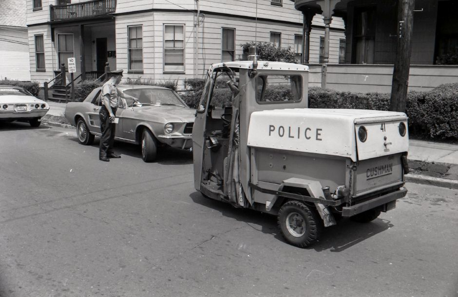 An officers tickets a mustang while driving around in a 3-wheel police vehicle, July 1975.