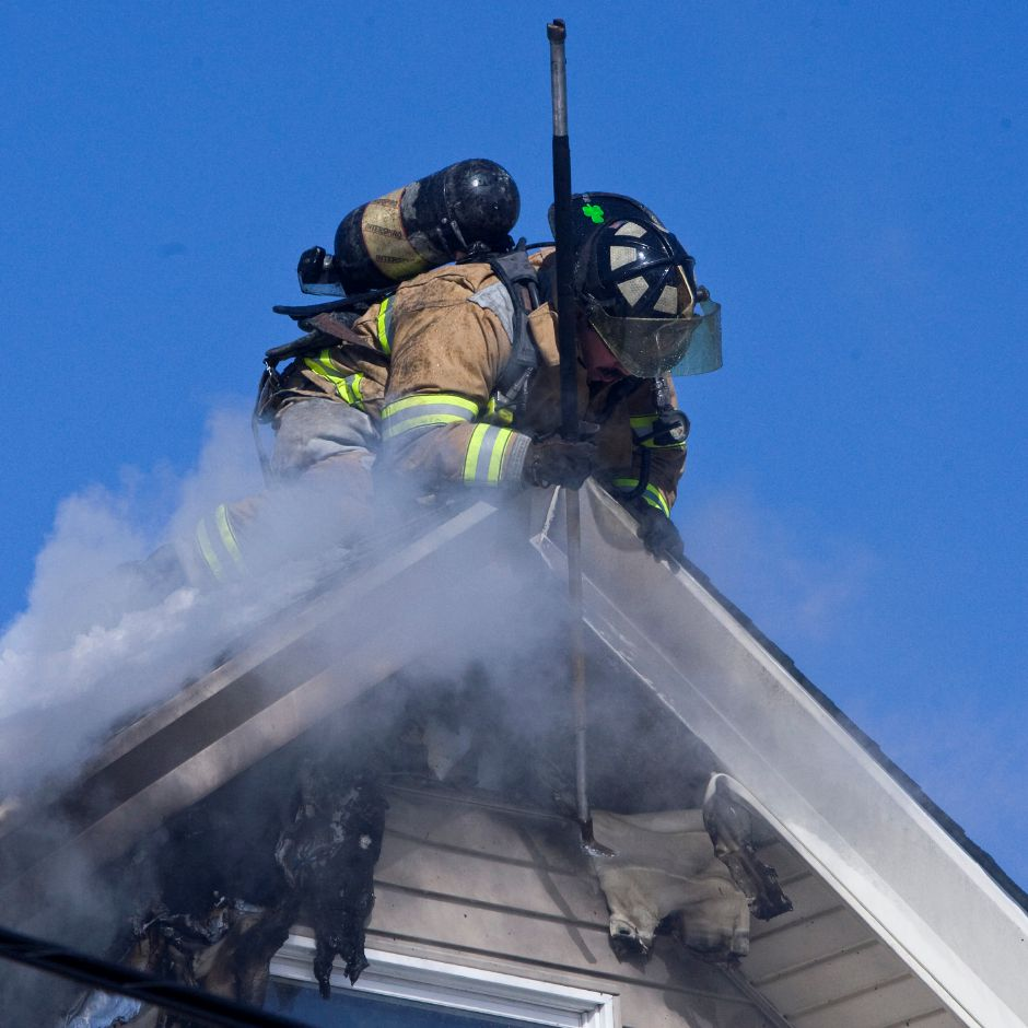 A firefighter from Co. 1 reaches over the peak of the roof to expose the smoldering wood on the house at 29 North First Street in Meriden, Wednesday morning, Mar. 4, 2009. (Christopher Zajac/Record-Journal)