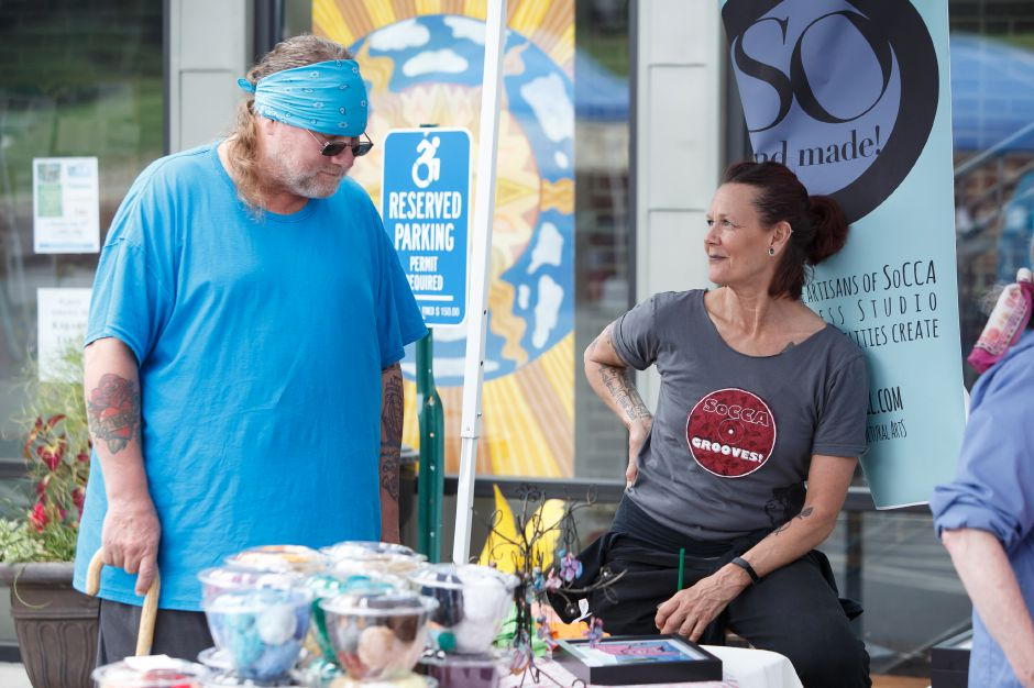 All Access director Lauri MacLean right talks with a patron Sunday during a Summer Sidewalk Sale at Southington Community Cultural Arts Center in Southington July 22, 2018 | Justin Weekes / Special to the Record-Journal