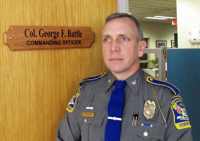 In this Thursday, March 8, 2018 photo, new Connecticut State Police Commander Col. George Battle poses for a photo at police headquarters in Middletown, Conn. Battle said he expects all troopers to be wearing body cameras by the end of the year. He also said he plans to maintain a focus on traffic safety and preventing accidents. (AP Photo/Dave Collins)