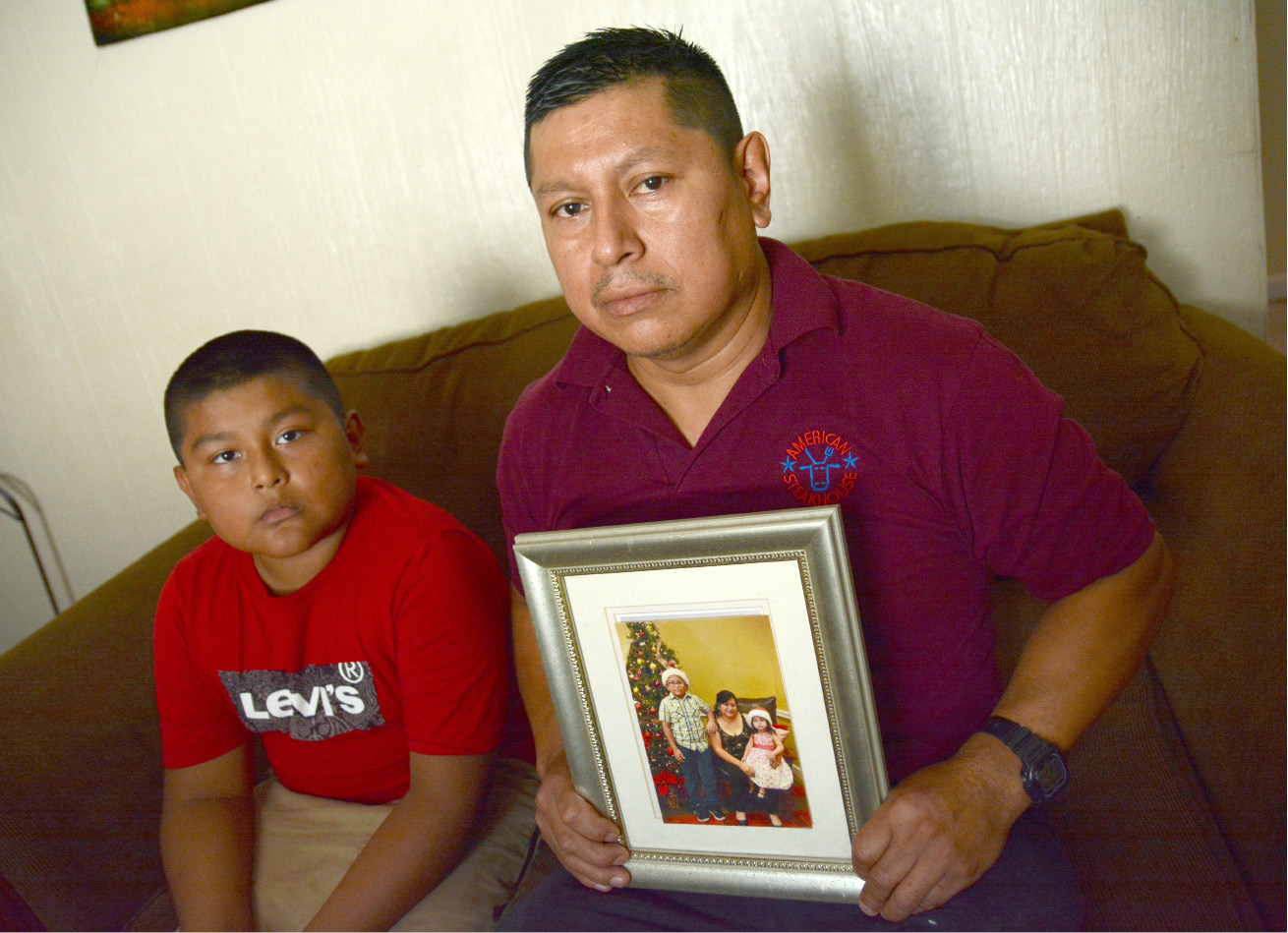 Meriden resident Cesar Quilligana holds a photo of his wife, Rosa Chabla, who was recently ordered by ICE to leave the country. His son, Jerry, sits next to him. | Bryan Lipiner, Record-Journal