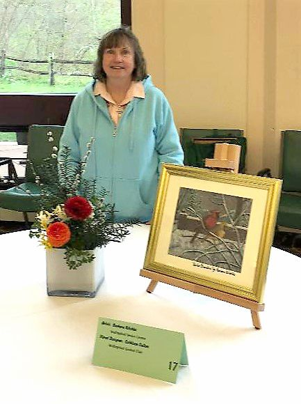 Cathleen Cullen created this floral display for a painting by artist Barbara Nitchke, and both are members of the Wallingford Garden Club.