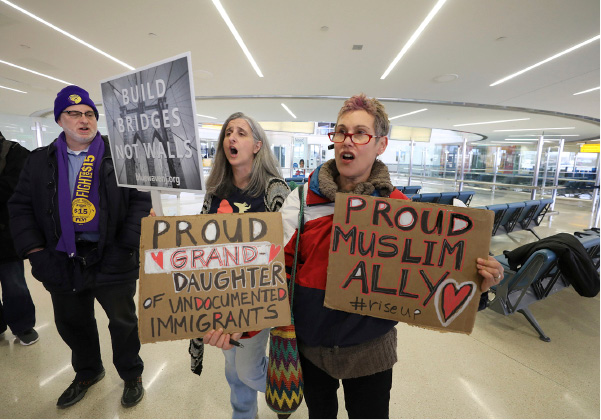 Kevin Brown of the Service Employees International Union, Kelly McDonald, of Montclair, and Jessica Sporn, of Montclair, chant in protest of the travel ban before the start of a press conference, Thursday, March 16, 2017, at Newark Airport, in Newark, N.J. (Chris Pedota/The Record via AP)