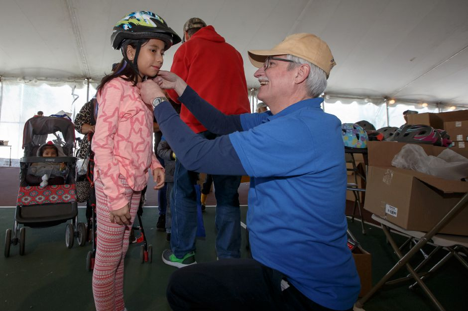 Yadira Balbuena 10 of Meriden gets fitted for a bike helmet from Kiwanis Club
