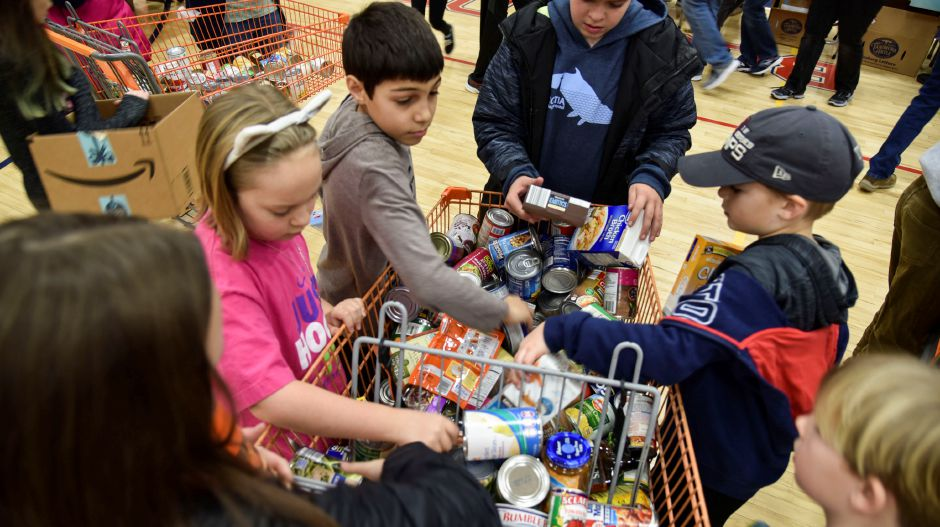 Community members help sort and pack up food donations at Coginchaug Regional High School, which were collected during the 13th annual Community Round-up in Durham and Middlefield on Saturday, Dec. 1, 2018. The event collected more than 13,000 food items and about $3,500 to go to Durham and Middlefield Social Services, and Amazing Grace in Middletown. | Bailey Wright, Record-Journal