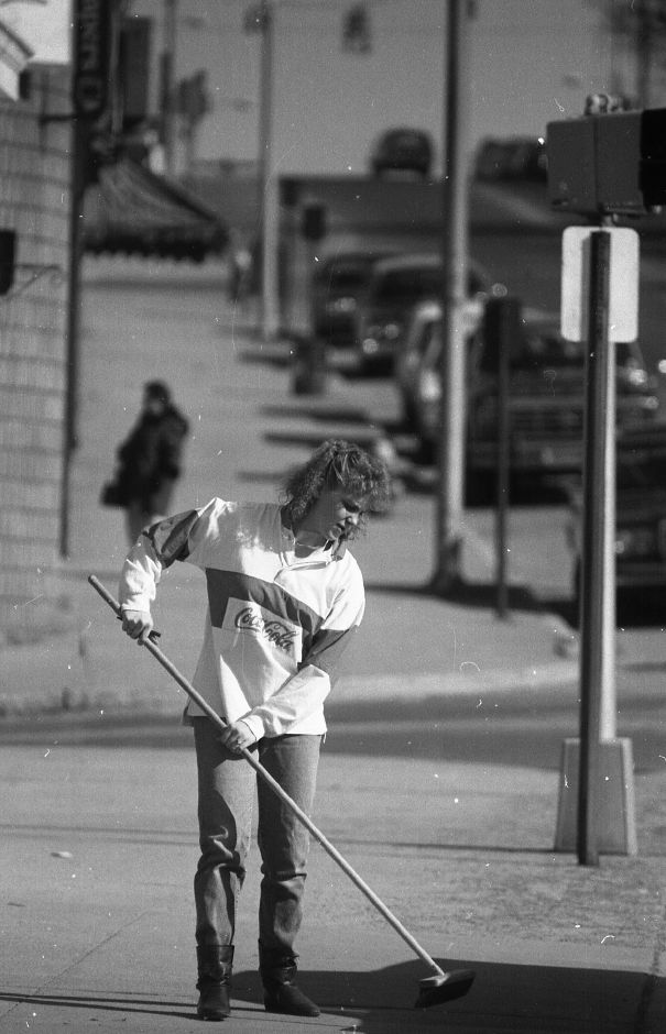 RJ file photo - Lori Lemieux takes advantage of the warmer weather by sweeping the sidewalk in front of the Center Street business where she works, March 10, 1989.