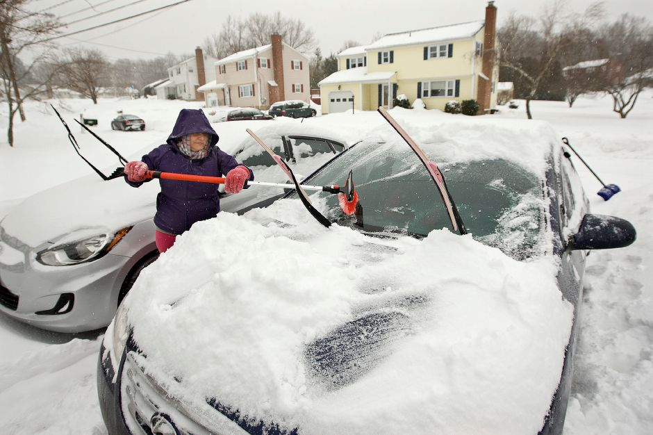 Iris Ramos, of Meriden, sweeps snow off her windshield at her residence on Tumblebrook Rd. during a winter storm in Meriden, Monday afternoon, February 9, 2015. Snow is expected to continue with varying intensity through the day. | Dave Zajac / Record-Journal