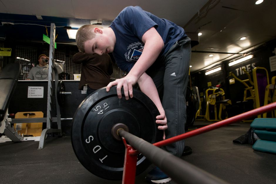 Luca Raccio adds weight to the bar during his power clean workout Saturday at Ultimate Sports in Wallingford. | Justin Weekes / For the Record-Journal