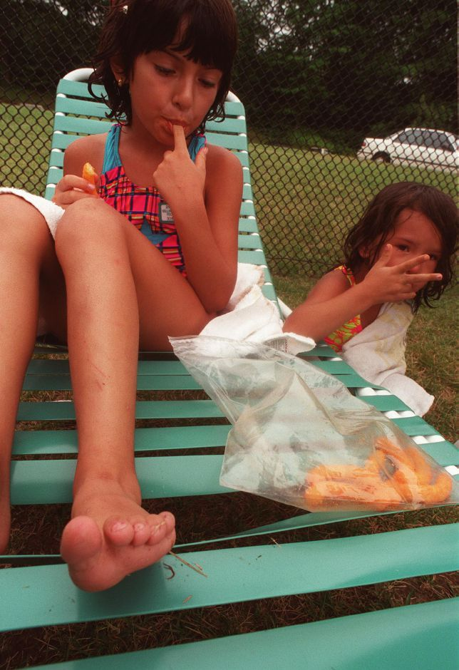Juliane Brusinski, 7, left, and Gabby Chung, 4, feast on cheese doodles while they dry off after a swim at the Community Pool in Wallingford.