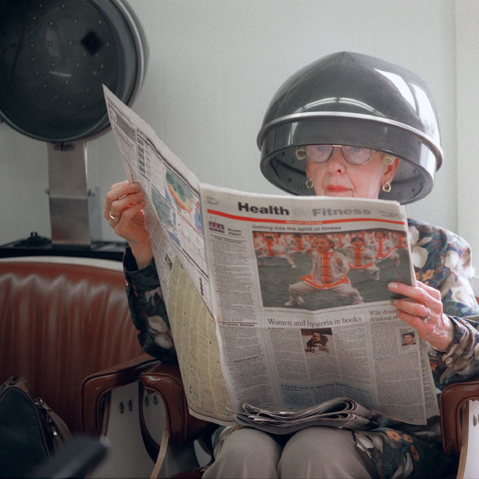 RJ file photo - Evelyn Devlin of Southington reads the Record-Journal newspaper while sitting under a hair drier at Delores