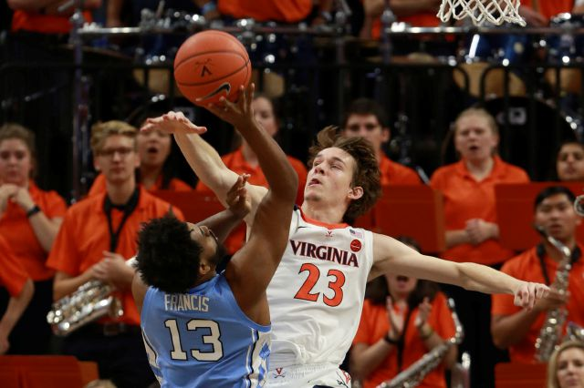 Virginia guard Kody Stattmann (23) blocks the shot of North Carolina guard Jeremiah Francis (13) during the second half of an NCAA college basketball game in Charlottesville, Va., Sunday, Dec. 8, 2019. Virginia defeated North Carolina 56-47. (AP Photo/Steve Helber)