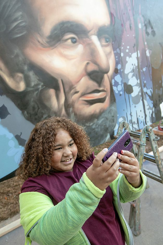 "Sixth-grade student Ciara Martin, 11, snaps a selfie with a portrait of Abraham Lincoln painted by global graffiti artist ""ARCY,"" of North Haven outside Lincoln Middle School in Meriden, Mon., Dec. 3, 2018. ARCY is known for large scale art he creates all over the world, and for organizations like Major League Baseball, Disney and the National Parks Service. Dave Zajac, Record-Journal"