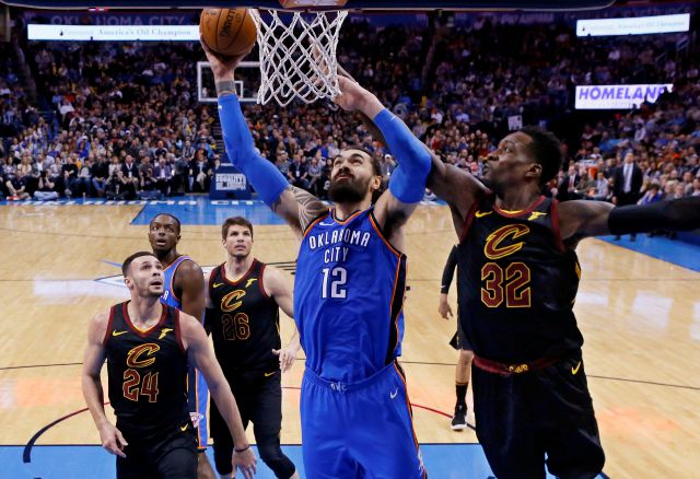 Oklahoma City Thunder center Steven Adams (12) shoots between Cleveland Cavaliers forward Larry Nance Jr. (24) and forward Jeff Green (32) during the first half of an NBA basketball game in Oklahoma City, Tuesday, Feb. 13, 2018. (AP Photo/Sue Ogrocki)