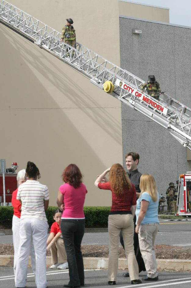 At Westfield Shoppingtown Meriden, employees of J.C.Penny stand in the parking lot while Meriden firefighters return from extinguishing a freight elevator fire Tuesday morning September 5, 2006. Chris Angileri/Record-Journal.