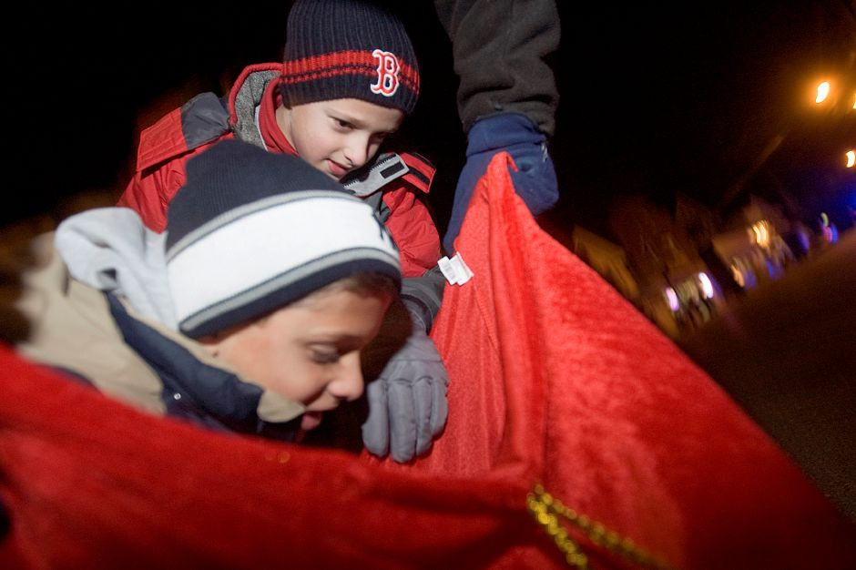 Matthew Mauro, 8, reaches down into a bag of candy canes held by Dave Harrington, a volunteer for Southignton Community Services while his twin brother, Daniel Mauro, 8, peers inside the bag of candy during the Christmas in the Village of Plantsville along West Main Street Thursday, November 2, 2010. (Johnathon Henninger/ Record-Journal)