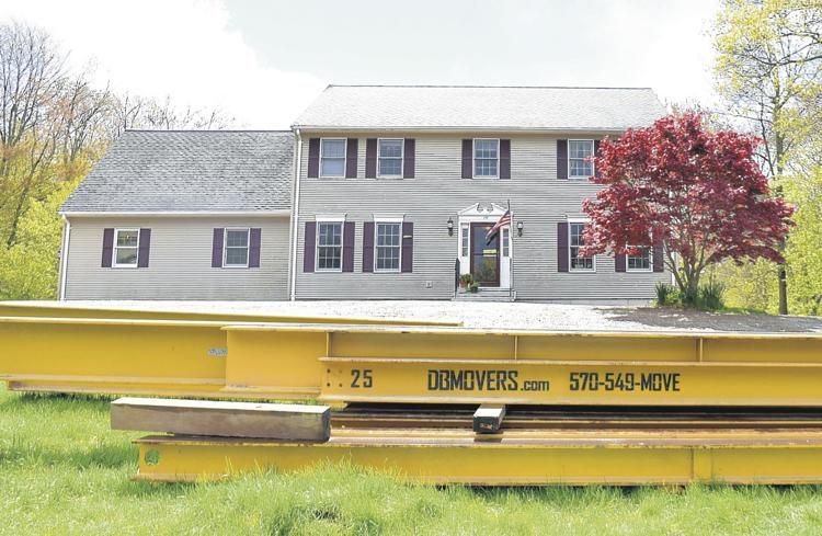 In the yard are the beams that were used to lift up the Tolland home of Kevin and Aisling McCloskey to replace their crumbling foundation.(Jim Michaud / Journal Inquirer)