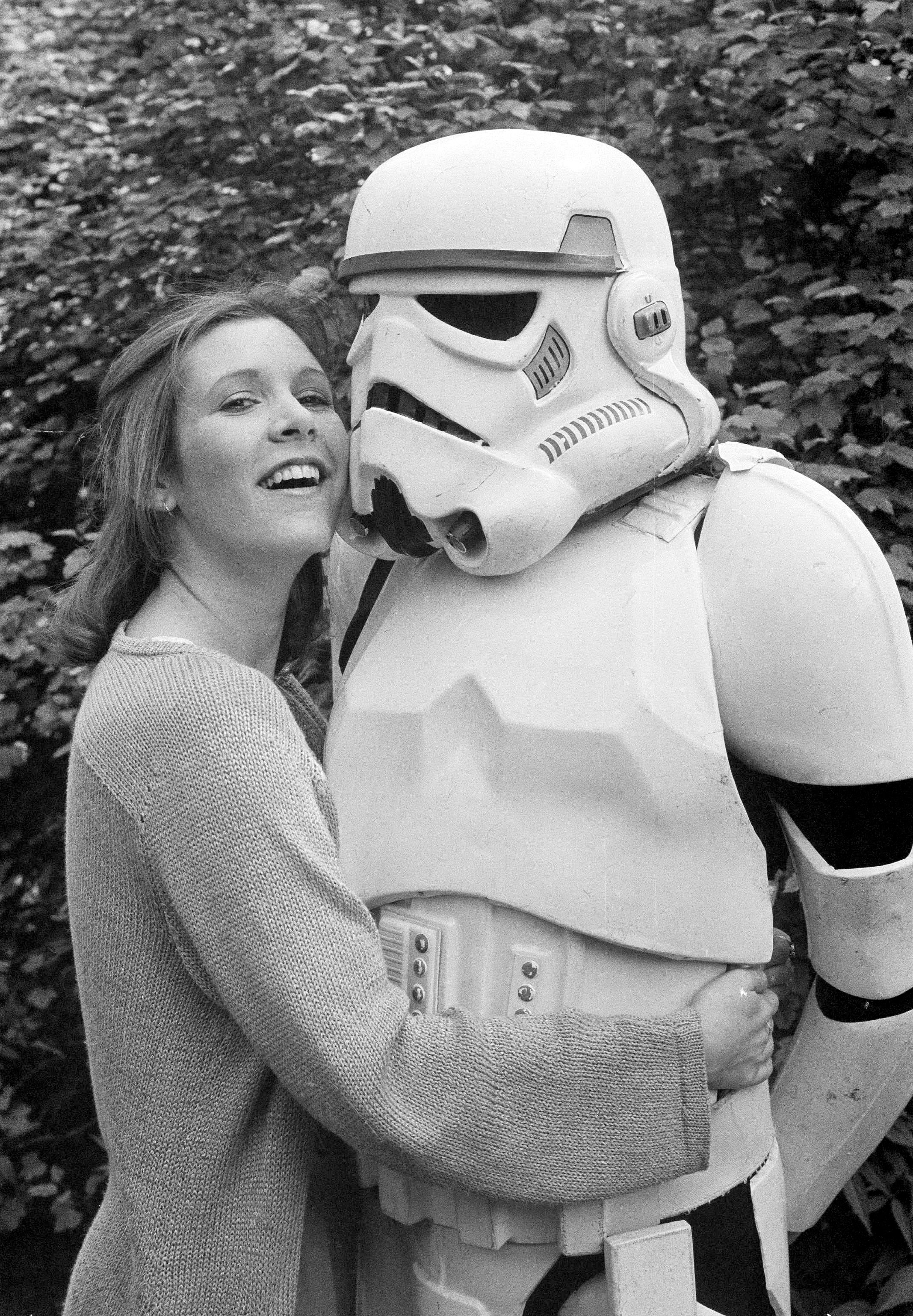 "FILE- In this May 23, 1980, file photo, actress Carrie Fisher hugs a person dressed as a stormtrooper in London while promoting the ""Star Wars"" epic ""The Empire Strikes Back."" Fisher, a daughter of Hollywood royalty who gained pop-culture fame as Princess Leia in the original ""Star Wars"" died Tuesday, Dec. 27, 2016. She was 60. (AP Photo/Dave Caulkin, File)"