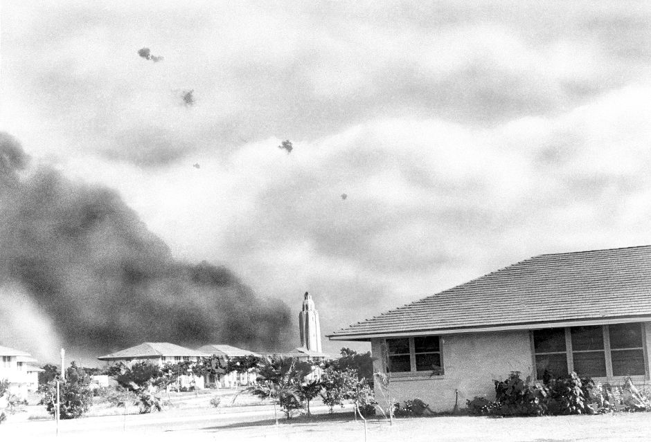 "A Japanese plane, braving American anti-aircraft fire, proceeds toward ""battleship row,"" Pearl Harbor, after other bombers had hit USS. Arizona, from which smoke billows, Dec. 7, 1941. (AP Photo)"
