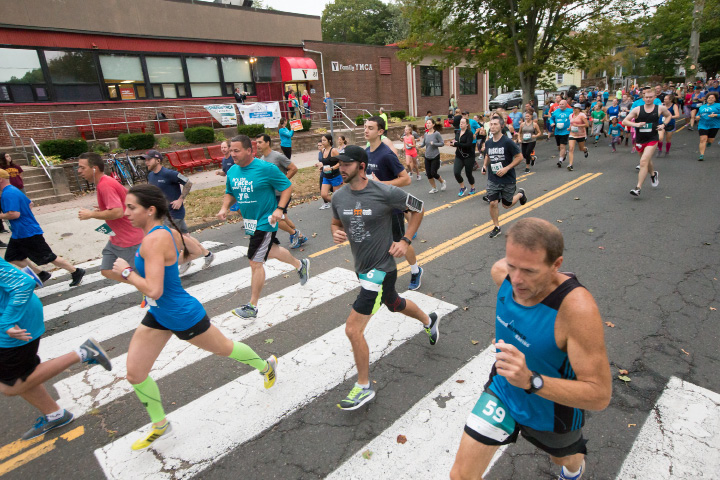 Runners pass the YMCA from the start Sunday during the Fishbein YMCA 10K and 5K road race in Wallingford. Runners and walkers started on South Elm and finished at the Town Hall. October 8, 2017 | Justin Weekes / For the Record-Journal