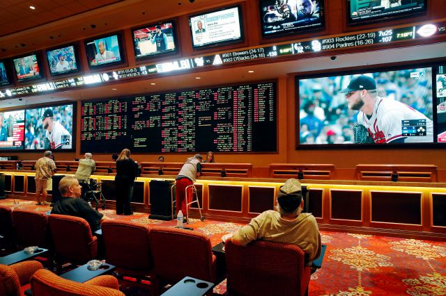 "FILE – In this May 14, 2018, file photo, people make bets in the sports book at the South Point hotel and casino in Las Vegas. A top New Jersey lawmaker, Democratic state Senate President Steve Sweeney, urged all 50 states on Wednesday, May 23, 2018, to reject ""integrity fee"" payments to professional sports leagues in any sports betting legislation, calling it ""extortion"" for leagues to demand money for hosting honest games. (AP Photo/John Locher, File)"