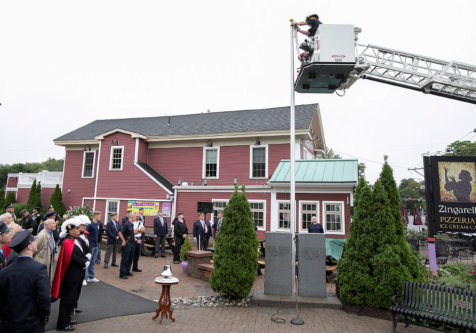 Firefighter Tom Golec of Ladder 1 assists in attaching rope to the flagpole prior to the annual 9/11 remembrance ceremony at the 9/11 memorial site along the Farmington Canal Heritage Trail in Southington, Tuesday, Sept. 11, 2018. Dave Zajac, Record-Journal