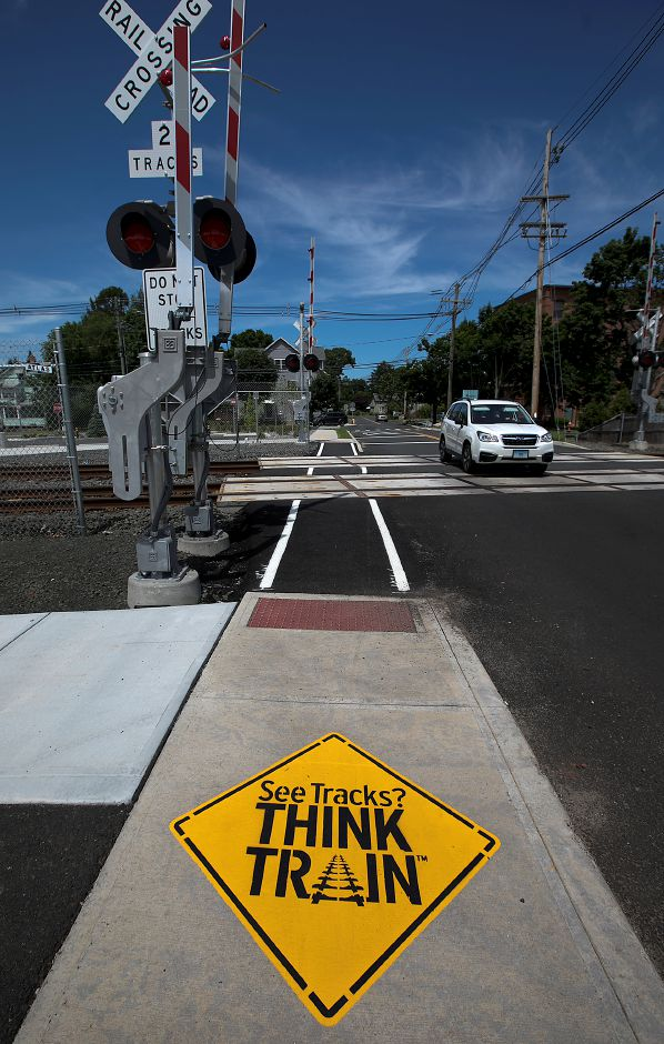 New signage  on the sidewalk warns pedestrians at the Parker Street rail crossing in Wallingford.