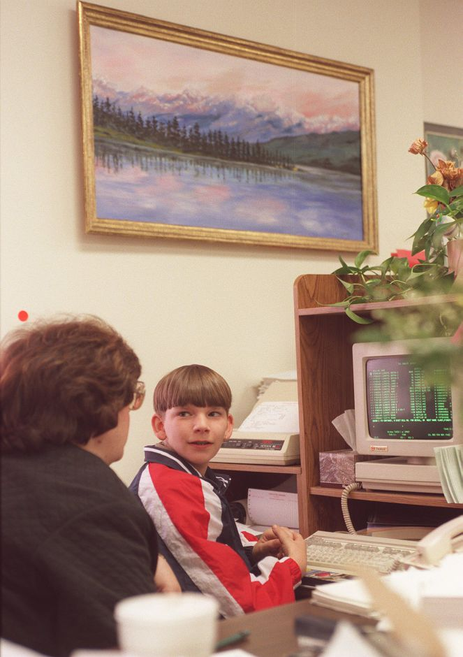 RJ file photo - Joanne Lorusso, left, teaches her nephew Ryan Christenson, 11, a student at Moran Middle School, about working in the tax department at Town Hall during Take Your Child to Work Day April 22, 1999.