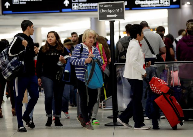Passengers wait in line at a security checkpoint at Miami International Airport, Friday, Jan. 18, 2019, in Miami. The three-day holiday weekend is likely to bring bigger airport crowds. (AP Photo/Lynne Sladky)