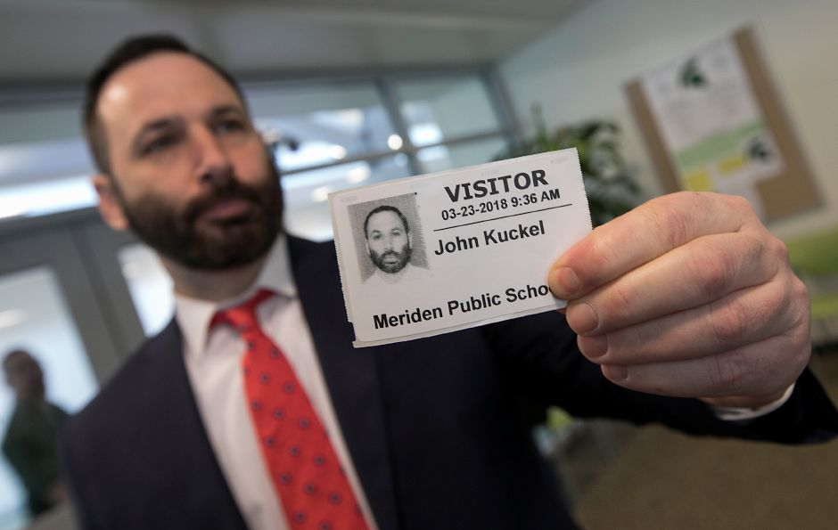 Assistant Principal John Kuckel shows an example of the new ID cards required for visitors at Maloney High School. City schools are using driver's license scanners to screen visitors. Schools also have added low-tech anti-shatter film on windows to deter potential intruders, and they've limited the number of student entrances to school buildings. Photos by Dave Zajac, Record-Journal