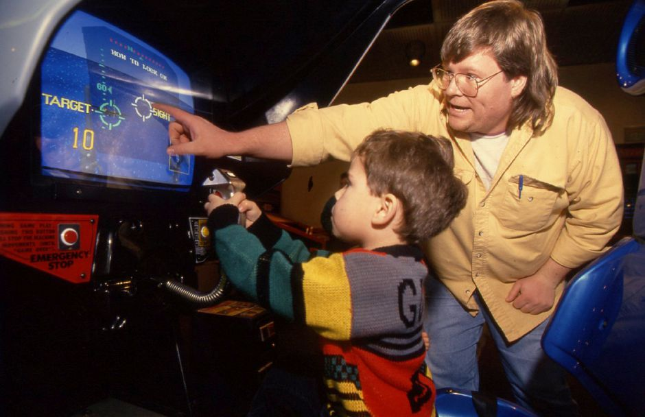 RJ file photo - Raymond Gloade, 4, plays a game called Fighter Pilot at the Time-Out arcade in the Meriden Square mall Jan. 6, 1994. His father, Bill Gioade of Bristol, offers some navigational advice.