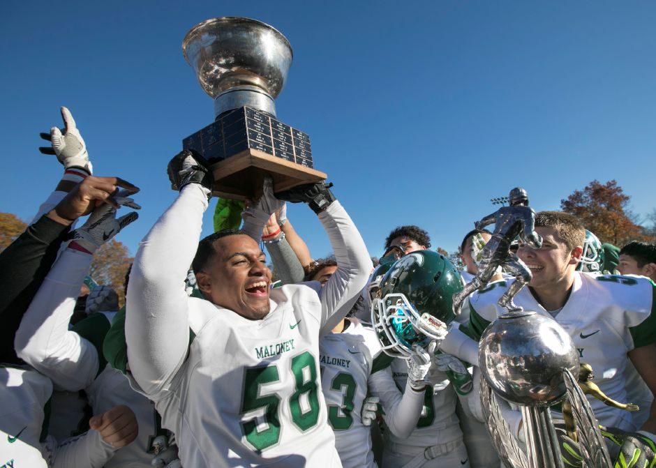 Maloney  linebacker Darlin Lopez hoists the Stoddard Bowl trophy after his team defeated Platt, 27-21, at Falcon Field in Meriden on Thanksgiving.Dave Zajac, Record-Journal